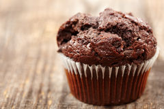 Chocolate muffin. Closeup of a chocolate muffin on a rustic wooden board Royalty Free Stock Images