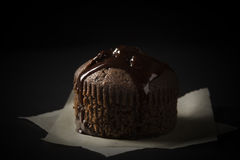 Chocolate muffin. Covered with chocolate sauce placed on a piece of baking paper on black background Stock Image