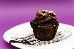 Chocolate muffin. Delicious homemade chocolate muffin on white plate and pink background Royalty Free Stock Photos