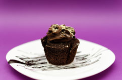 Chocolate muffin. Delicious homemade chocolate muffin on white plate and pink background Stock Photography