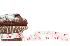 Chocolate Muffin Diet. Chocolate chip muffin with a measuring tape Royalty Free Stock Images