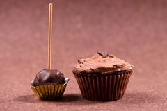Chocolate muffin with hazelnut minty cream and ice cream topping. Isolated on brown background Stock Image