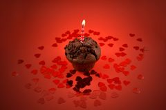Muffin with candle stock images. Chocolate muffin with heart on a red background. Sweet birthday pastry. Valentines Day concept Stock Photos