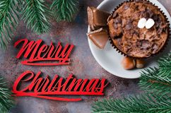 Chocolate muffin and Merry Christmas inscription. Chocolate muffin, branches fir and Merry Christmas inscription. Xmas time. Selective Focus. Copy space Stock Photography