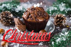 Chocolate muffin and Merry Christmas inscription. Chocolate muffin, branches fir and Merry Christmas inscription. Xmas time. Snow effect. Selective Focus. Copy Royalty Free Stock Photography
