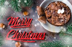 Chocolate muffin and Merry Christmas inscription. Chocolate muffin, branches fir and Merry Christmas inscription. Xmas time. Snow effect. Selective Focus. Copy Royalty Free Stock Photo