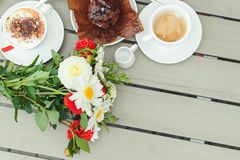 Chocolate muffin with one candle, cups with coffee on wooden table . Chocolate muffin with one candle, cups with coffee on the wooden table Stock Image
