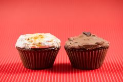 Chocolate muffin and one vanilla cupcake isolated on red background Stock Images