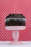 Chocolate Muffin. A chocolate muffin on a pink dessert stand pedestal against a  fun background in a dessert shop royalty free stock photo