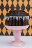 Chocolate Muffin. A chocolate muffin on a pink dessert stand pedestal against a  fun background in a dessert shop stock photo