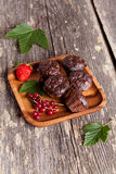 Chocolate muffin with red currant on wooden background. Vertical, close up Stock Images