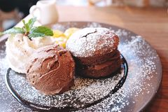 A Chocolate muffin served with chocolate ice cream, whipped cream and banana, that`s topped with caramel syrup. On wooden background Stock Photos