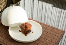 Chocolate muffin under the ceramic salver over white dish. Syrup covered chocolate muffin under the ceramic salver over white dish Royalty Free Stock Photography