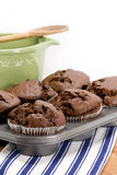 Chocolate Muffins. Chocolate chocolate chip muffins freshly out of oven cooling on blue and white striped kitchen towel, green mixing bowl in background royalty free stock photos