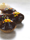 Chocolate muffins. A variety of muffins with a chocolate topping and colorful candies stock images