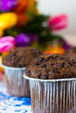 Chocolate muffins on the background of tulips. Chocolate muffins on the board written under gzhel Stock Photo