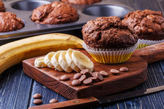 Chocolate muffins with banana on dark background. Chocolate muffins with banana on dark background, selective focus Royalty Free Stock Photos