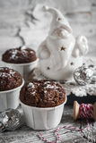 Chocolate muffins and ceramic Santa Claus on a light wooden surface Stock Photos