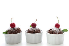 Chocolate muffins with cherry and leaves of mint on white backgr Stock Images