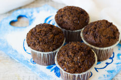 Chocolate muffins with chocolate chips. Chocolate muffins on the board written under gzhel Royalty Free Stock Photography