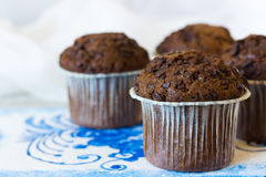 Chocolate muffins with chocolate drops. Chocolate muffins on the board written under gzhel Royalty Free Stock Photos