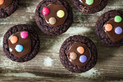 Chocolate muffins with chocolate glaze decorated with colourful drops on wooden background Royalty Free Stock Photography