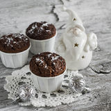 Chocolate muffins and Christmas decoration ceramic Santa Claus on a light wooden surface Royalty Free Stock Photography