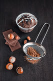 Chocolate muffins with cocoa , chocolate bars and hazelnuts Royalty Free Stock Images