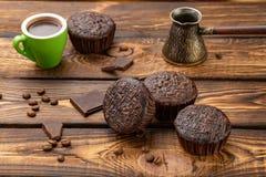 Chocolate muffins on broun wooden background. The Chocolate muffins with coffe and chocolate stock photo