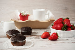 Chocolate muffins, coffee, strawberries, a vase of white flowers. Light wood rustic background Royalty Free Stock Images