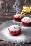 Chocolate muffins on a dark background with icing sugar stock photography