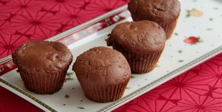 Chocolate muffins with dark cocoa and gingerbread spices. Christmas cakes. Chocolate muffins with dark cocoa, gingerbread spices and plum butter. Served on Stock Images