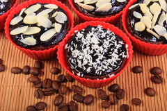 Chocolate muffins with desiccated coconut and almonds, coffee grains Royalty Free Stock Photography