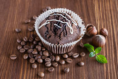 Chocolate muffins with hazelnuts and coffee beans. On wooden background stock images