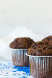 Chocolate muffins on a light background. Chocolate muffins on the board written under gzhel Royalty Free Stock Photography