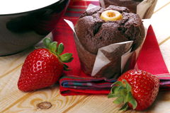 Chocolate muffins with milk and strawberries. Black cup filled with milk chocolate muffins, strawberries on pine wood Stock Images