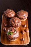 Chocolate muffins with nuts, decorated with mint, top up. Chocolate muffins with nuts, decorated with mint, vertical, close up Royalty Free Stock Images