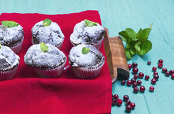 Chocolate muffins in paper sprinkled with powdered sugar. On a light wooden table in rustic style, some chocolate muffins in paper sprinkled with powdered sugar Royalty Free Stock Photo