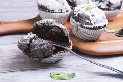 Chocolate muffins in paper sprinkled with powdered sugar. On a light wooden table in rustic style, some chocolate muffins in paper sprinkled with powdered sugar Stock Photo
