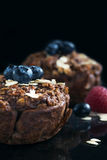 Chocolate muffins with raspberries, bluesberries and oat on dark background. Royalty Free Stock Images
