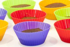 Chocolate muffins in silicone holders of many colors Stock Images
