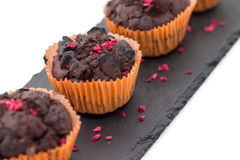 Chocolate muffins on slate plate isolated on white. 4 pieces of fresh homemade chocolate muffins in orange wrapping paper with dehydrated raspberries on rough Royalty Free Stock Photos
