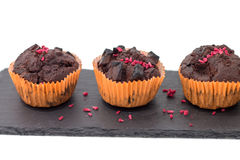 Chocolate muffins on slate plate isolated on white. 4 pieces of fresh homemade chocolate muffins in orange wrapping paper with dehydrated raspberries on rough Royalty Free Stock Photo