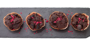 Chocolate muffins on slate plate isolated on white. 4 pieces of fresh homemade chocolate muffins in orange wrapping paper with dehydrated raspberries on rough Stock Photos
