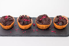 Chocolate muffins on slate plate  on white. 4 pieces of fresh homemade chocolate muffins in orange wrapping paper with dehydrated raspberries on rough-looking Royalty Free Stock Photo