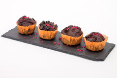 Chocolate muffins on slate plate  on white. 4 pieces of fresh homemade chocolate muffins in orange wrapping paper with dehydrated raspberries on rough-looking Stock Photos