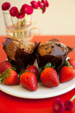 Chocolate muffins with strawberries Stock Photos