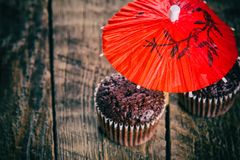 Chocolate muffins under red umbrella Stock Image