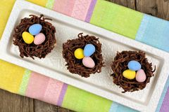 Chocolate nests with candy eggs on colorful Easter table cloth. Plate of springtime chocolate nests filled with candy eggs on colorful Easter table cloth Royalty Free Stock Photography
