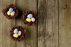 Chocolate nests with candy eggs on rustic wood Royalty Free Stock Image